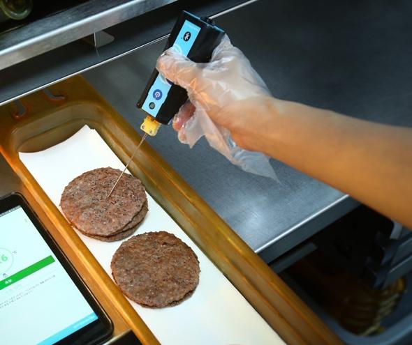 디지털 온도계를 사용하여 조리 후 패티의 중심 온도를 측정하는 모습.jpeg